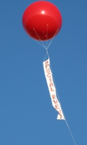 8 feet in diameter red color helium advertising balloon in sky with attached banner