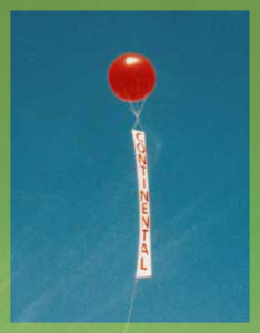 red helium advertising balloon with vertical banner